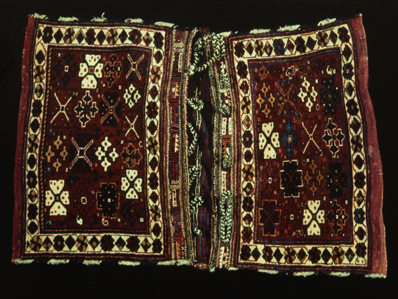 Saddle bag; Hehbelik. Wool. Embroidered areas at top are decorated with squares, crosses, and triangles of red, green, brown, blue and white wool. Herringbone borders at top of black, brown, and white goat hair. Woven fabric and embroidery.