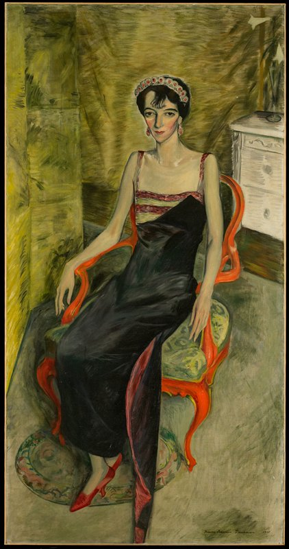 Portrait. Seated woman in red and black dress, red shoes, and matching headband/earrings. White dresser with flowers in upper right background.