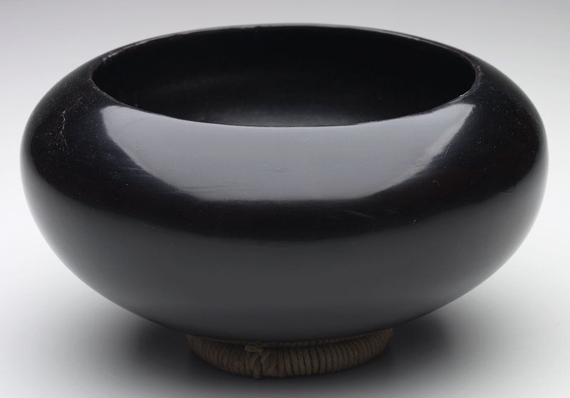 round body with rounded bottom and inward-turning lip; black lacquer; rests on fiber-covered ring