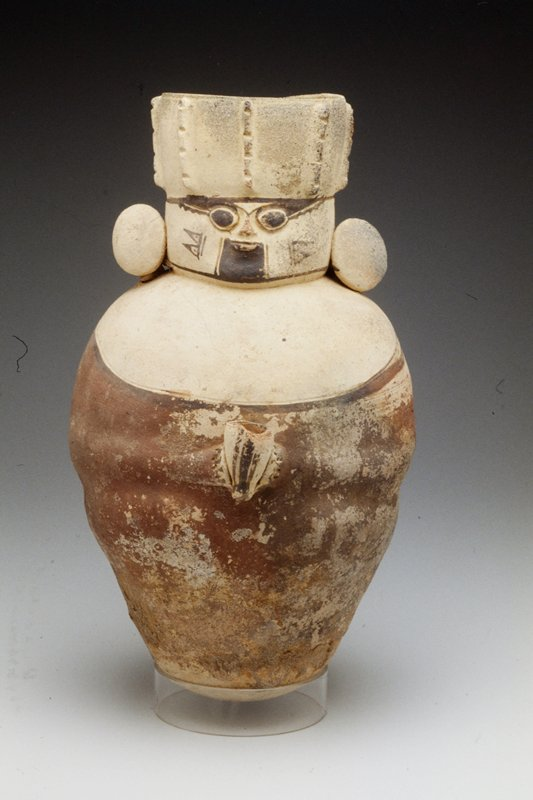 round-bottomed pitcher in shape of human figure with tall headdress and earplugs, holding in his hands a small vessel; polychromed clay in white, red and brown.
