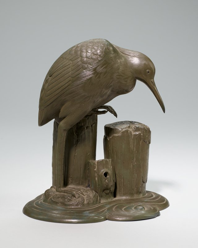 figure of heron standing in water with three logs; pottery, green
