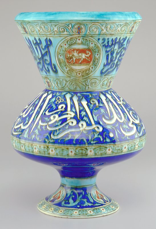 Light yellow interior; short, bulbous body resting on a splaying foot with a flaring wide neck; neck decorated with 3 circular cartouches surrounding horses with crowns on their backs and dark blue pseudo-Islamic text against a light blue ground; white 'text' and foliage on body; floral designs on foot