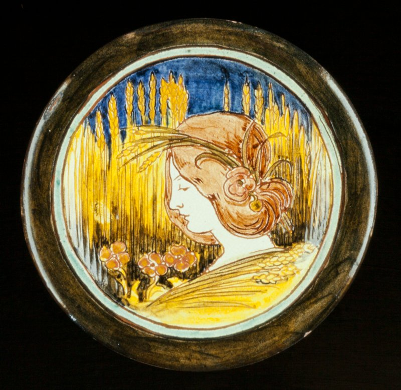Della Robbia Dish, ceramic, design shows woman's head with garland of wheat, this super-imposed on a wheat-field backgorund, incised design, blue, rose, green, yellow, white glazes, pooter, red clay