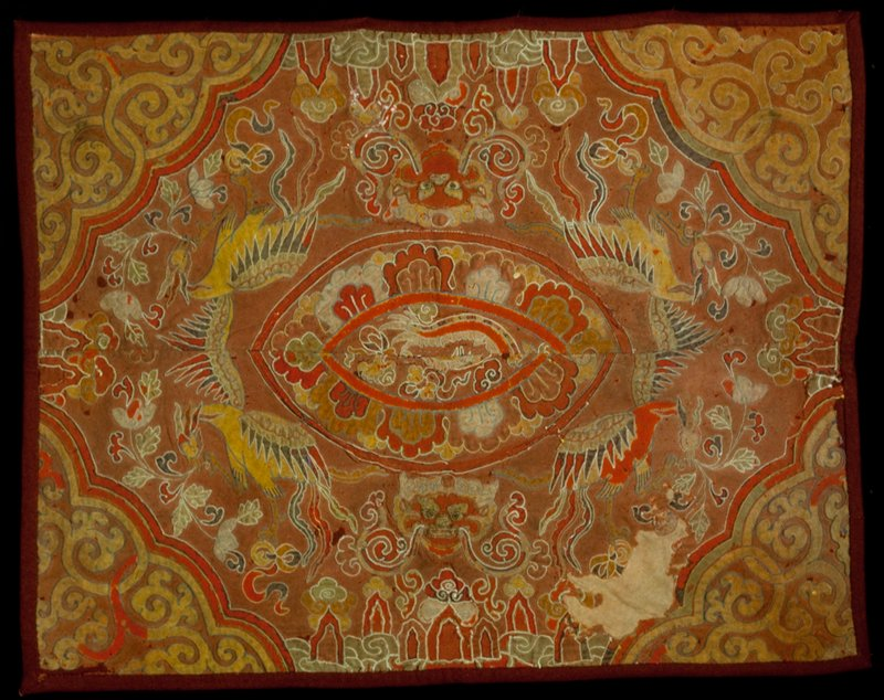 Tikhep (throne cover); cotton; applique design of birds, animal faces and flowers on dull red ground; with wool backing