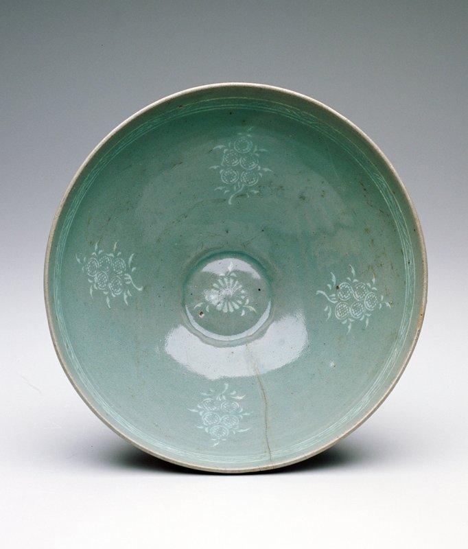 bowl four floral medallions underglazed with white slip; celadon glaze