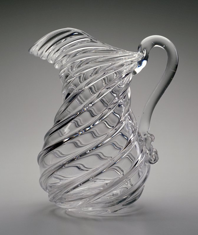Pitcher, lead glass, applied handle, eight swirled ribs, dip molded. Technique also described as pillar molding.