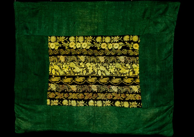 Pillow cover, central panel of assembled sari borders. Green silk border, red silk lining. Accessioned retroactively for Dec. 17,1985 at meeting of Mar. 11, 1986