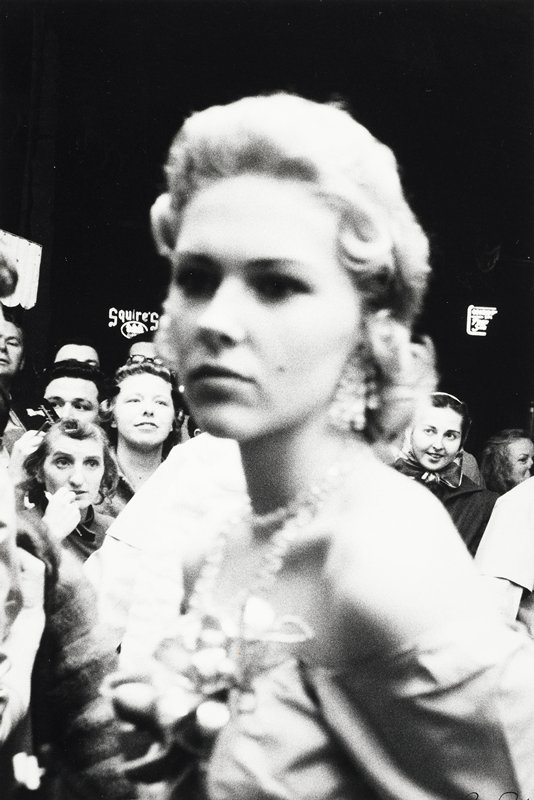 close up of blonde woman with corsage, crowd in background