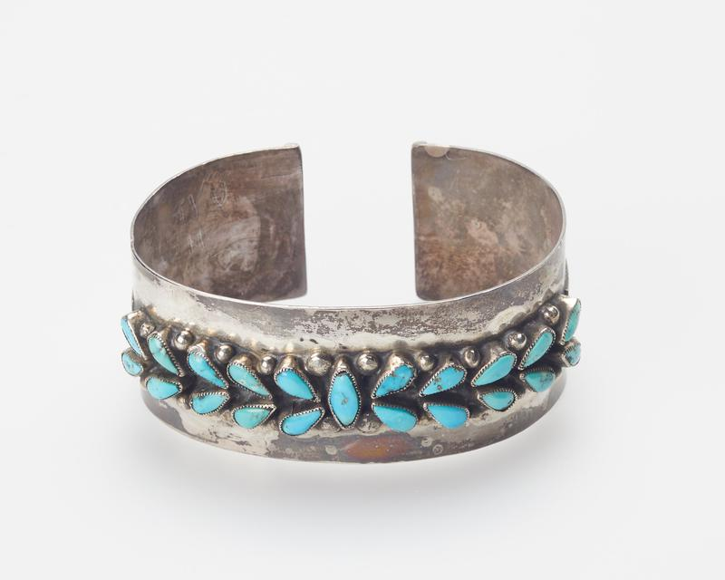 New Zuni. Silver Band set with one elliptical and twenty small pear-shaped turquoises in serrated bezels; teardrop applique, and stamped decoration J.#333, Cat.#343.