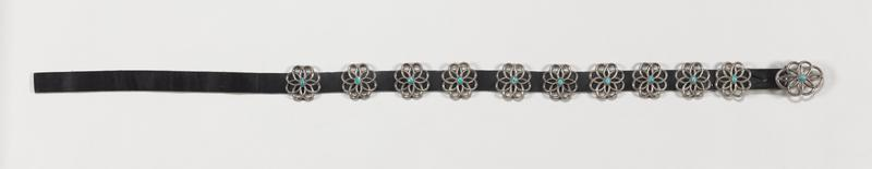 Leather belt with cast openwork silver buckle, 10 silver conchas; conchas are cast, floral design, with sm. oval Morenci turquoise set in plain bezel in center of each; 11 stones in all; twisted wire decoration. J.#540, Cat.#571.