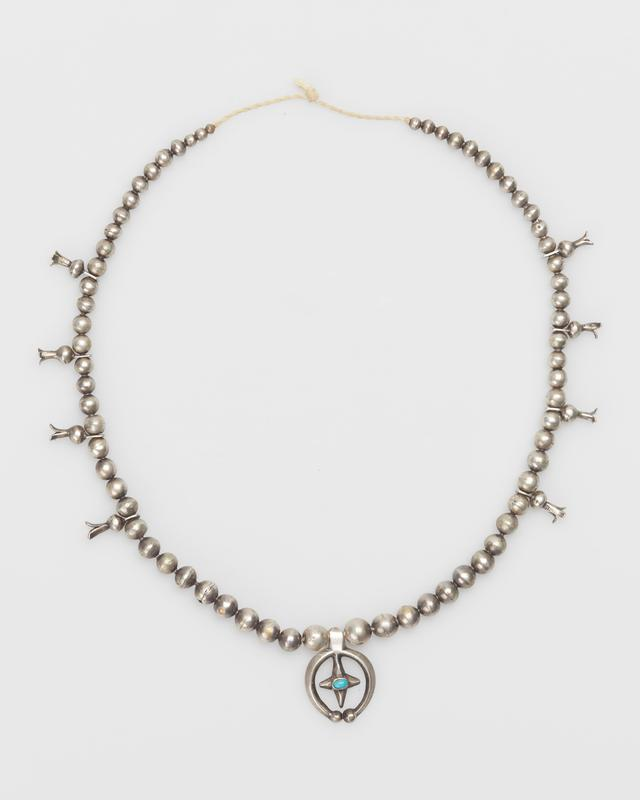 """Santa domingan. Single strand of silver beads; on either side of naja are 5 3-pronged squash-blossoms attached to bead and pierced extension with 3-sectioned decorative """"butterfly"""" plate set with elliptical Blue Gem Turquoises on top, one turquoise in center of each plate;cast naja is carinated, has 3 turquoise, fleur-de-lis and shell decoration; string has metal clasp; 13 stones. J.#408, Cat.#425."""
