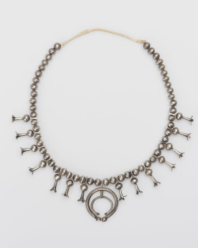 naja possibly about 1900, beads about 1930. Single strand of silver beads; fourteen squash blossom beads; hammered double carinated naja with stamped and repousse decoration (one button broken off). J.#487, Cat.#392.