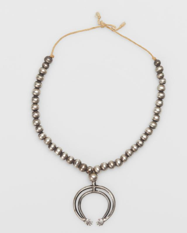 Single strand of medium silver beads with cast double 82 band naja ending in pair of hands, strung on string. J.#454, Cat.#374.