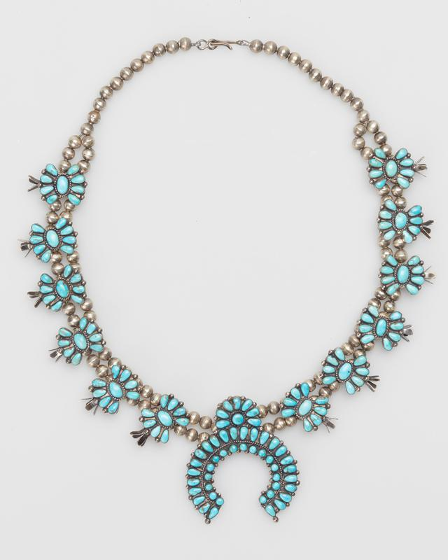 Double strand of silver spherical beads; twelve squash blossoms overlaid with cluster of oval and elliptical Morenci turquoises; sheet naja set with double row of round and oval Morenci turquoises; serrated bezels; twisted wire and teardrop decoration. J.#475, Cat.#399.
