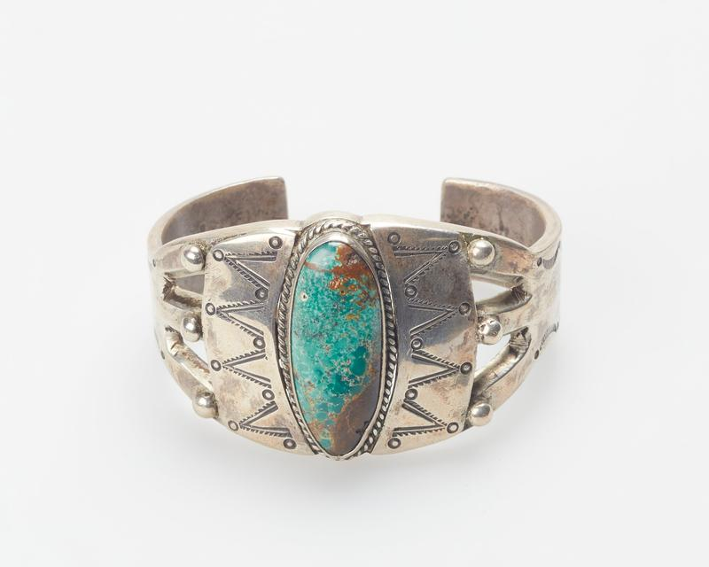 Heavy split band; set with single large elliptical turquoise; stamped applique, teardrop, and twisted wire decoration; Band set with single green turquoise, stamped design cat. 43,J#13