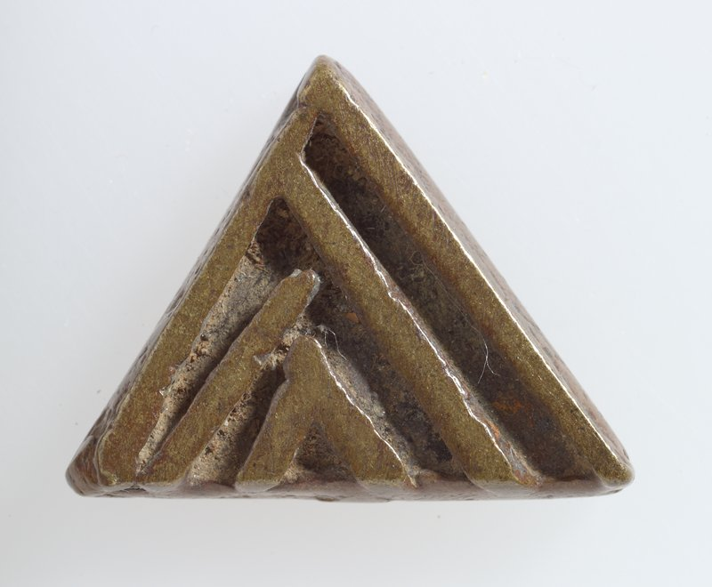 One of 37 gold weights, bronze, various sizes; pattern upright traingle with three lines following the shape on each side;