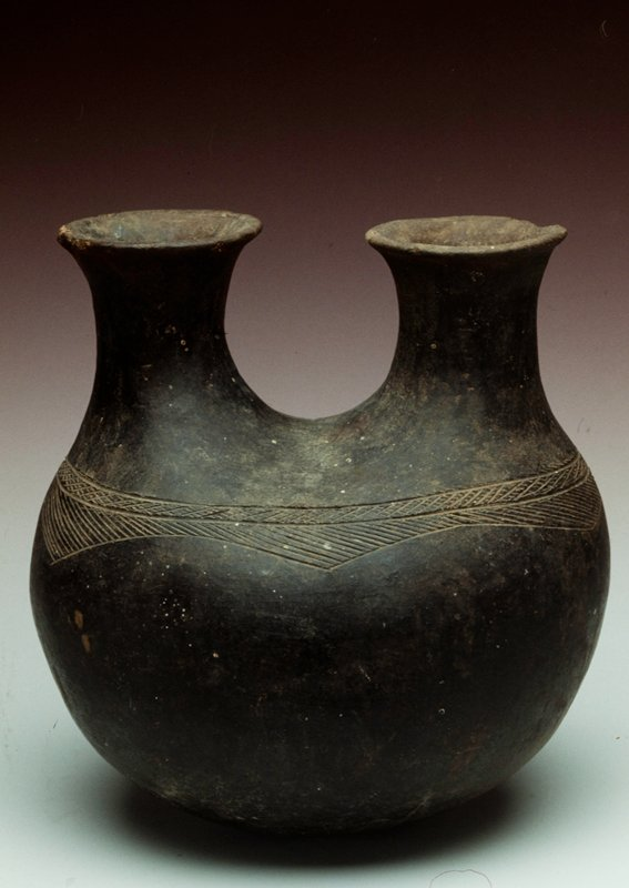 Vessel with two necks. Incised ring around shoulder. Dark brown/black in color