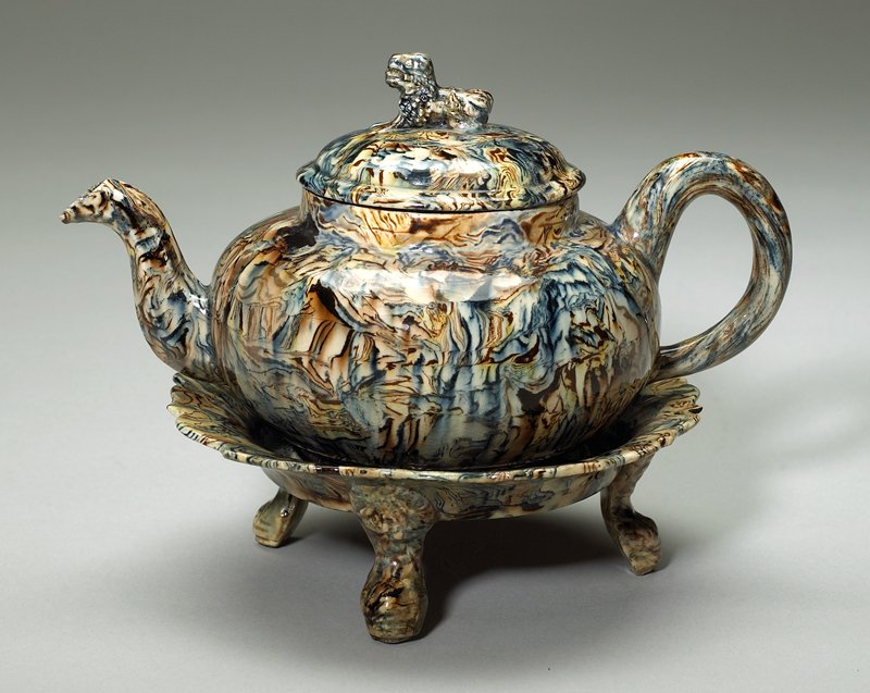 globular shape with S shaped spout and loop handle, cover with lion finial, circular stand with scalloped rim and three paw feet, blue and brown marbelized pattern on mud-yellow ground