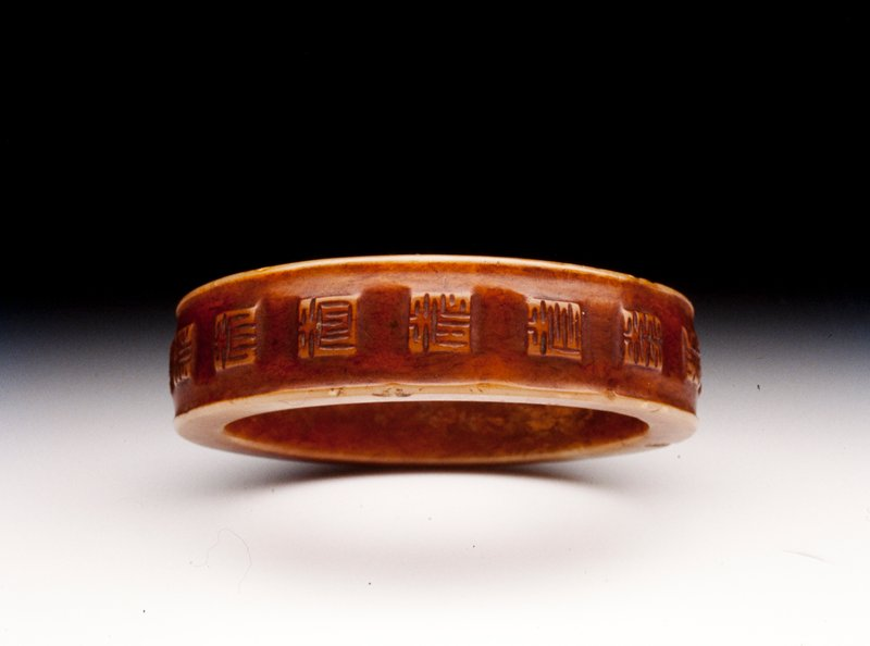 nephritic jade bracelet of good brown/russet color simply carved with 16 ideograms, all variations of 'Shou' or long life and with a slightly beaded edge