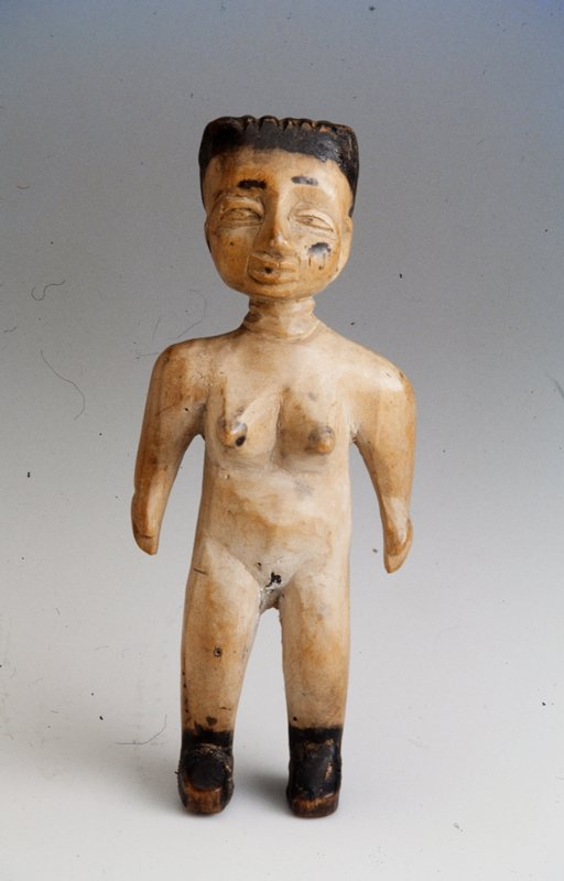 Standing wooden female figure; back and top of head are flat; black hair, facial features, and shoes;
