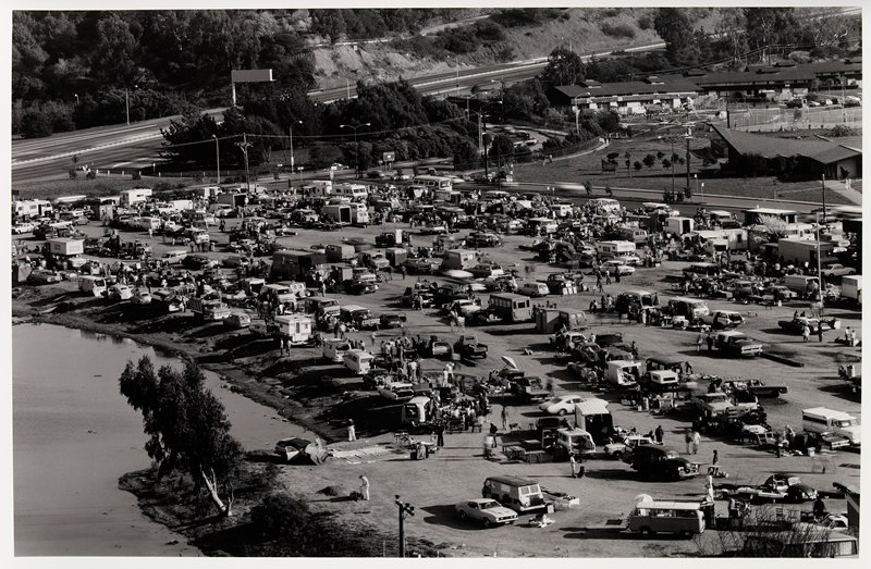 parking lot filled with cars and people