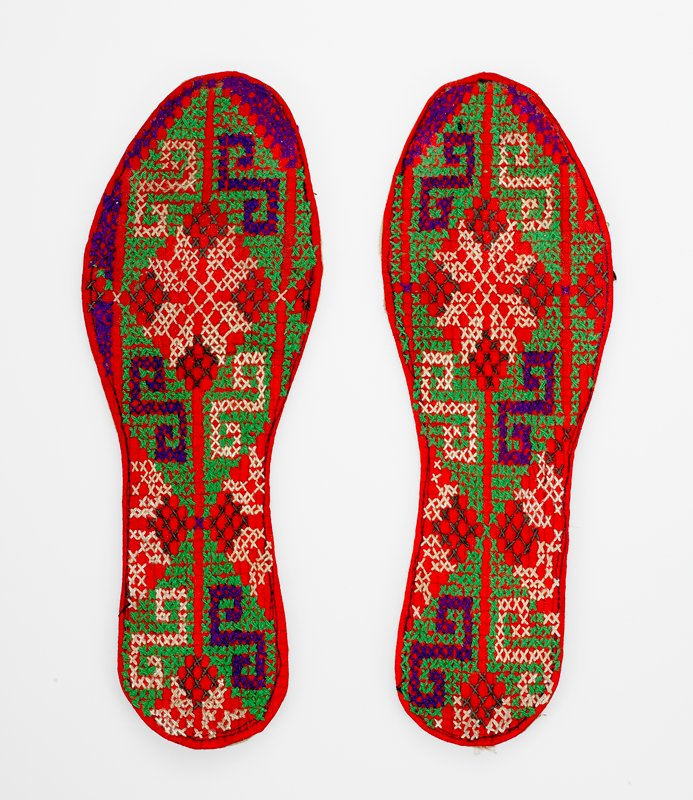 red ground, cross stitched design in purple, green, dark and white threads