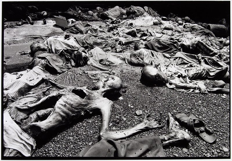 large group of decomposing bodies on pebbled ground; one sandle is shown in LR corner