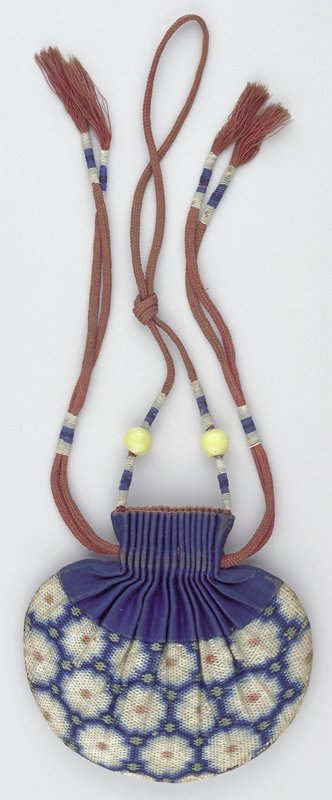 bag body decorated by three bands of blue, green, white and red geometric flower designs; top of purse is dark blue and looks like an accordion; two pull strings attached to either side of top with carrying string coming from the top