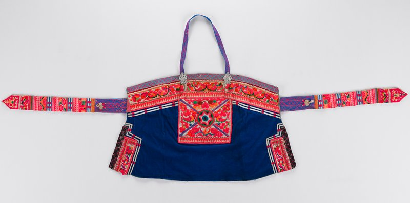 blue corduroy apron with embroidered on tie strap; also heavily embroidered on top front; small mirror in center of front; metal decorations at ends of neck strap