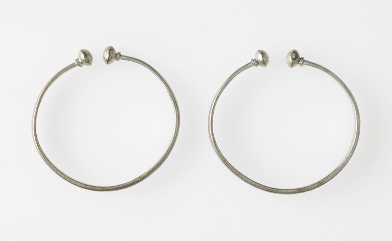 two almost identical circular bands; bands are not continuous but have a small opening with round ends; dragon and phoenix motif with Chinese character in center