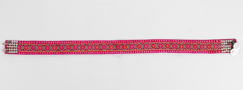 fuchsia embroidered belt with metal balls on each end; two coins sewn next to buttons on one end