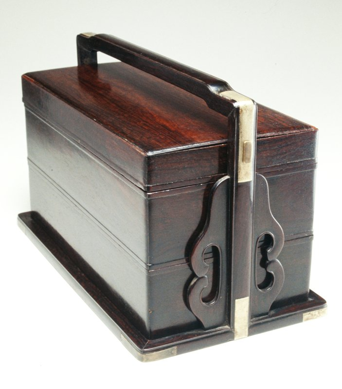 box with two removable tiers and lid on a base fastened by a long pin through the lid