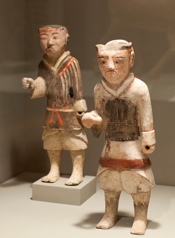 standing figure with right hand out in front and clenched, left hand down at hip; triangular heads with black features painted on pink ground; .1 wearing a breast plate over baggy trousers; .2 wearing a striped tunic over baggy trousers