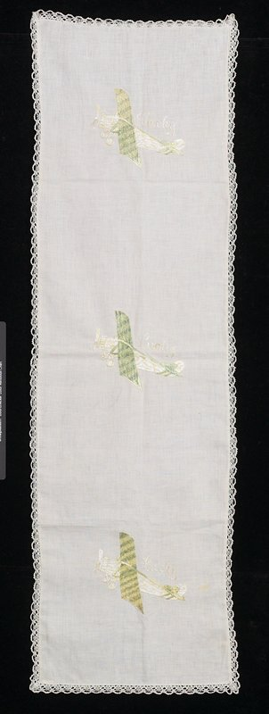 embroidered with a bobbin lace edging; imagery refers to 'Lucky Lindy' Charles Lindberg flying The Spirit of St. Louis; three plane images
