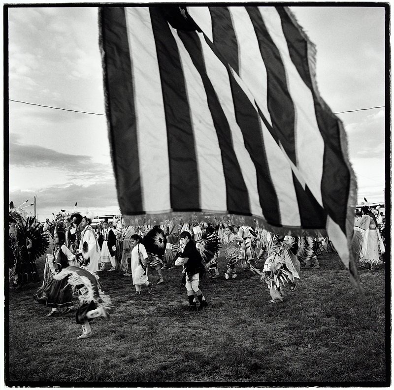 Native Americans gathered together wearing traditional clothing, seen under the stripes of an American flag and to either side