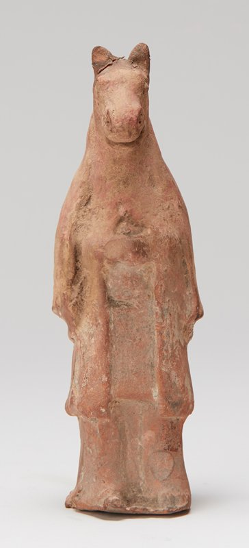ceramic standing figure with horses head wearing a cloak; reddish brown clay; traces of brown pigment