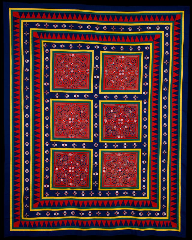 hanging was completed in the Ban Vinai Refugee Camp in Thailand; reverse applique and embroidery; saw tooth borders pointing out, blue border with vegetable blossom designs; six squares in central area with heart and snail patterns