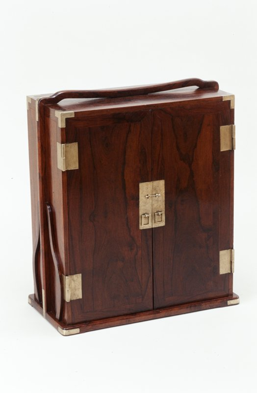 huang hua-li book carrying case; double door, square hinges, handles and corner hardware; interior of three shelves and bank of three drawers slightly above center; decorative frame with handle similar to picnic boxes