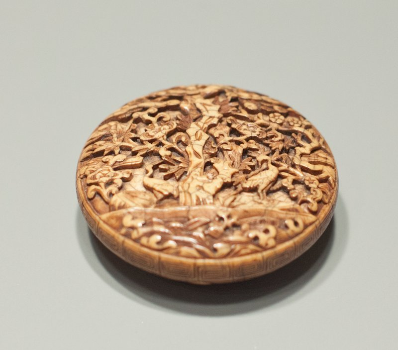 carved ivory finial; upper surface has garden scene with central stone column and two cranes at ground line looking back at each other; meandering patterned band at side; five circles encompassing a floral pattern at underside; circular hole at underside center