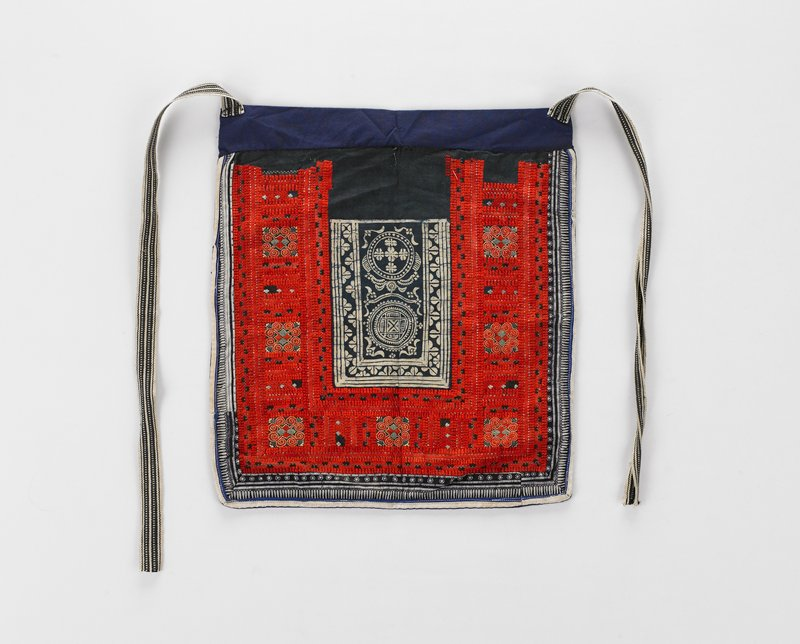 rectangular panel, ties at upper corners; batik band at sides and lower edge also a rectangular area at center with two circular designs and border reflective of outer border; red and black embroidery between batik, squares with diamond and curl patterns in gold thread