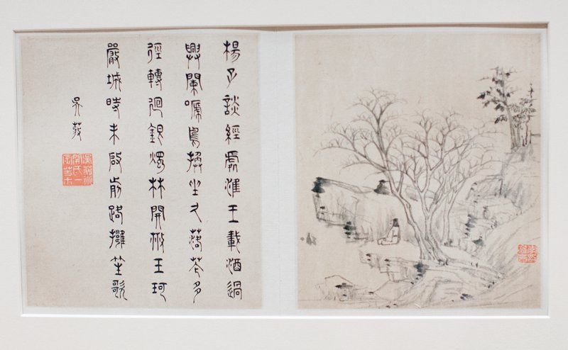 three larger trees in middle foreground; smaller leafier trees in URQ; rocky cliffs beneath leafy trees; rocky cliffs in LLQ; person sitting on middle of L hand rocks; chop mark in LR area; four columns of calligraphy characters plus characters above one large chop mark to L of columns accordian style album, wood covers; eight images, alternating with text, single page of text at end