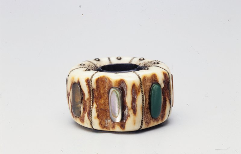 oval shaped irregular ivory ring divided into sections with decorated brass wire; studs around central opening at top and bottom with oval stones of various colors and materials set in each section on side