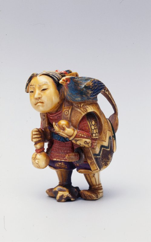 boy dressed in armor with hair in a ponytail, holding a ball in his proper left hand and a small purse in his proper right hand; blue pheasant on his proper left shoulder; polychromed