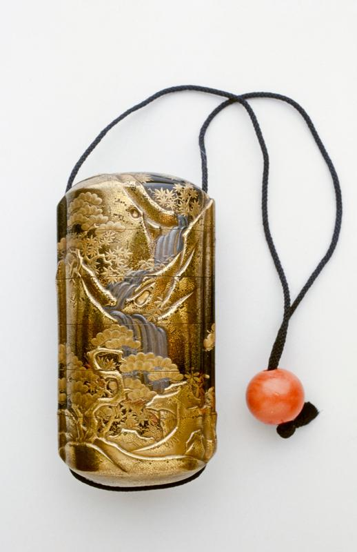 decorated overall with landscape of pines, maples and waterfall; dark blue cord and reddish-orange bead