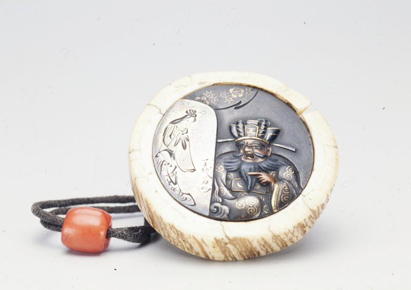 metal disk depicting man with moustache and beard parted into thirds pointing at a painting of a fashionable maiden; metal disk attached with cord to ivory holder which is made to resemble round section of a tree; red-orange bead on cord
