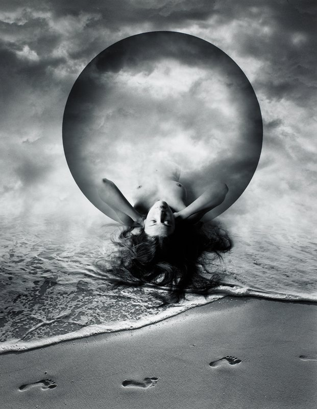 footprints in sand and half a woman's body hanging from sphere above water