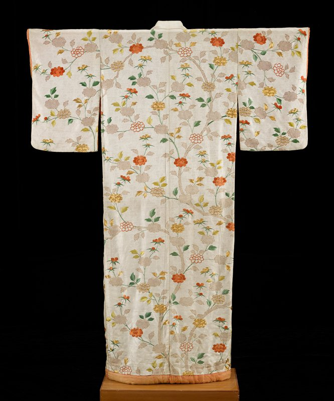 white ground printed with shiburi leaves in brown and embroidered with bamboo and flowers in orange, green and gold; lined with orange silk and stuffed at lower hem