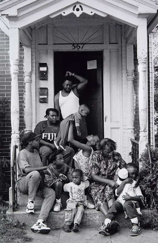 black and white photo of four women, five children, one man on front steps