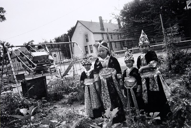 black and white photo of four girls in tradition costumes standing in yard next to swingset