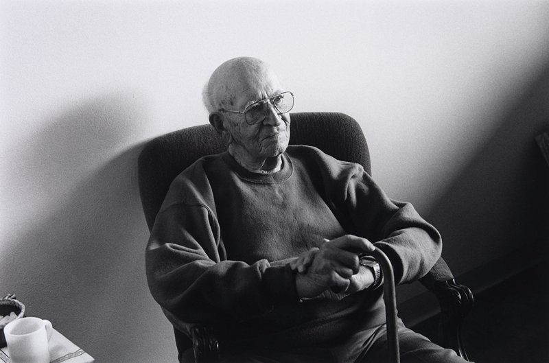 black and white photo of old man seated